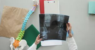Orthopedic surgeon doctor is making his paperwork writing description of the x-ray image sitting at his workplace.