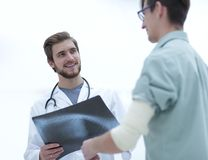 Orthopedic surgeon examining an x-ray of the patient. Standing in hospital corridor Stock Photos