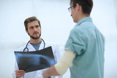 Orthopedic surgeon examining an x-ray of the patient. Standing in hospital corridor Stock Image