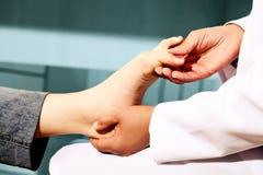 Orthopedische arts in zijn bureau met het model van de voeten royalty-vrije stock afbeelding