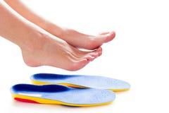 Orthopedische binnenzolen en vrouwelijke benen stock afbeeldingen