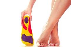 Orthopedische binnenzolen en vrouwelijke voeten stock afbeeldingen