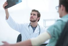 Orthopedist που εξετάζει μια ακτηνογραφία ενός ασθενή Στοκ Εικόνες