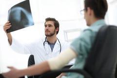 Orthopedist που εξετάζει μια ακτηνογραφία ενός ασθενή Στοκ εικόνα με δικαίωμα ελεύθερης χρήσης