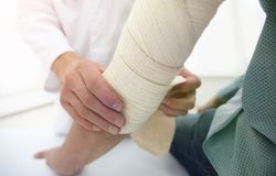 Orthopedist applying bandage onto patient`s hand in clinic. Closeup stock photography