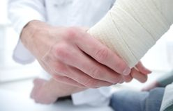 Orthopedist applying bandage onto patient`s hand in clinic. Closeup stock image