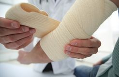 Orthopedist applying bandage onto patient`s hand in clinic. Closeup royalty free stock photography