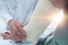 Orthopedist applying bandage onto patient`s hand in clinic. Closeup stock photo