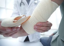 Orthopedist applying bandage onto patient`s hand in clinic. Closeup stock photos