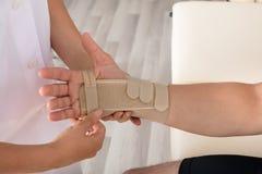 Orthopedist het Bevestigen Pleister op Gelaedeerde` s Hand stock fotografie
