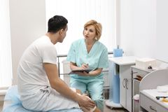 Orthopedist and patient with bandaged leg in hospital stock photos