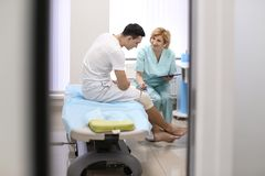 Orthopedist and patient with bandaged leg in hospital stock images