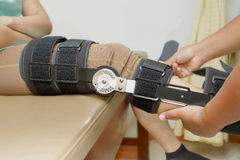 Orthopedist secures leg brace on knee, knee brace support for le Royalty Free Stock Photography
