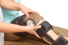 Orthopedist secures leg brace on knee Royalty Free Stock Photography