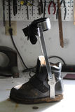Orthotic sko med det fäste benstaget på en arbetsbänk arkivfoton