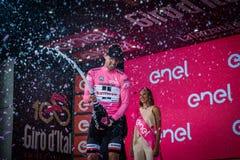 Ortisei, Itália 25 de maio de 2017: Tom Doumulin, no jérsei cor-de-rosa do melhor cavaleiro, no pódio após uma fase dura do monta Fotografia de Stock Royalty Free