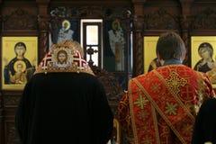 Ortodox biskop och ärkediakon som framme ber av altaret royaltyfri foto