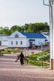 Ortodox kristen nunna som går med trädgårds- hjälpmedel förbi den inre borggården av kloster royaltyfria foton
