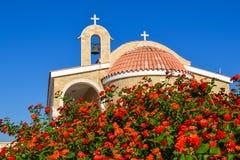 Ortodox kyrka med ett belagt med tegel tak och en klocka Röda rosor i förgrunden cyprus Ayianapa Kyrka av St-epiphanyen Royaltyfri Bild