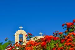 Ortodox kyrka med ett belagt med tegel tak och en klocka Röda rosor i förgrunden cyprus Ayianapa Kyrka av St-epiphanyen Royaltyfria Foton