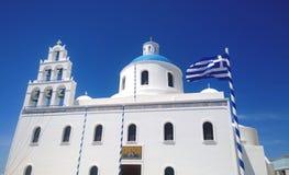 Ortodox kyrka Panagia i byn av Oia i Santorini med framkallning av flaggan arkivfoto