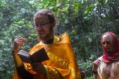Ortodox präst under sakrament av andlig födelse - dop Arkivfoto