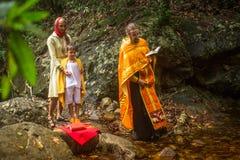 Ortodox präst under sakrament av andlig födelse - dop Arkivbild