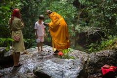 Ortodox präst under sakrament av andlig födelse - dop Fotografering för Bildbyråer