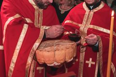 Serbian ortodox holy handmade bread. Ortodox priests in red robes with holy bread in hands on ceremony stock photography