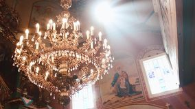 Ortodoxo, cristianismo, iglesia El haz de luz brilla sobre la lámpara vieja del gondel con las velas que cuelgan desde arriba de almacen de video