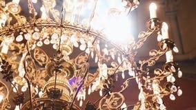 Ortodoxo, cristianismo, iglesia El haz de luz brilla sobre la lámpara vieja del gondel con las velas que cuelgan desde arriba de almacen de metraje de vídeo