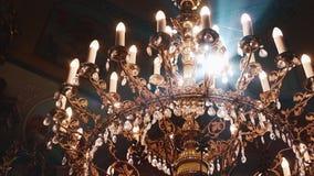 Ortodoxo, cristianismo, iglesia El haz de luz brilla sobre la lámpara vieja del gondel con las velas que cuelgan desde arriba de metrajes