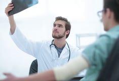 Ortopeda egzamininuje radiograph pacjent Zdjęcie Stock