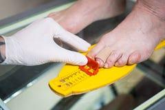 Ortopedi och medicin Ung Caucasian form för mätning för format för handskar för latex för tatuering för doktorshandman av foten f royaltyfri foto