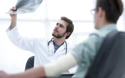 Ortopedico che esamina una radiografia di un paziente immagini stock