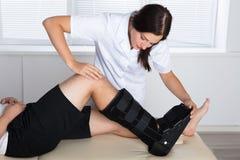 Ortopedico che regola gancio di camminata sulla gamba paziente del ` s immagini stock libere da diritti
