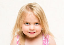 Ortrait of beautiful blonde toddler baby girl with cheeky grin Stock Photos