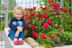 Ortrait of cute little girl near the flowers in Royalty Free Stock Image