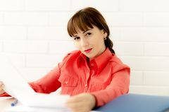 Ortrait der jungen glücklichen lächelnden Geschäftsfrau, die mit Dokumenten im Büro arbeitet stockbild