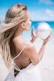 Ortrait der schönen blonden langen Haarbraut im Hochzeitskleiderstand eines offenen Rückens auf dem weißen Sandstrand mit einer P Lizenzfreie Stockfotos