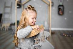 Ortrait eines glücklichen lächelnden Mädchens, das eine Geschenkbox öffnet stockbild