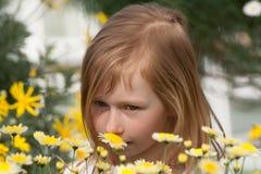 Ortrait eines kleinen Mädchens sieben Jahre alt, Schnüffelngänseblümchen Lizenzfreies Stockbild