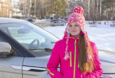 Рortrait of a girl with a red cap with a pompom ,standing near the car Royalty Free Stock Photo