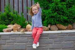 Ortrait gullig liten flicka nära blommorna i gård Royaltyfri Bild