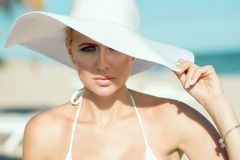 Ortrait van schitterende dame in witte bustehouder en breed-brimmed hoed bij de kust kijkend recht stock afbeeldingen