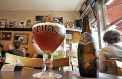 Orval Trappist Belgian Ale bottle and glass on a table stock photo
