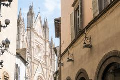 Orvieto. Italy-april 28,2018:view of the facade of the cathedral of  from one of its narrow streets during a sunny day Royalty Free Stock Photo