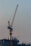Orzando la gru a torre del fiocco al cantiere del condominio sopra la st Fotografie Stock
