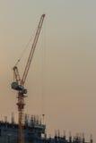 Orzando la gru a torre del fiocco al cantiere del condominio sopra la st Fotografia Stock
