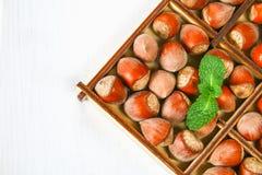 Orzechów włoskich hazelnuts w kwadratowym drewnianym pudełku z dividers na białym drewnianym stole obrazy stock